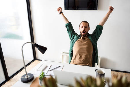 advise: Tired man is gaping in office