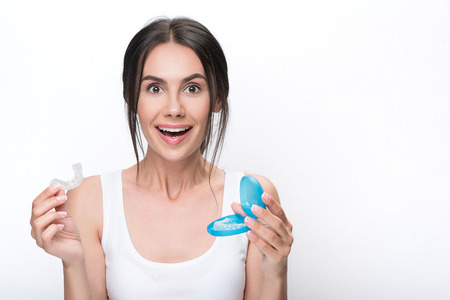 Happy young woman presenting clear aligners Stock Photo
