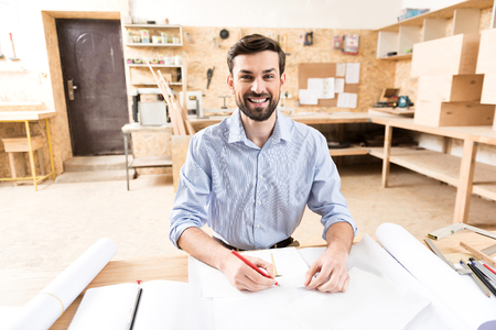 Cheerful wood master with beard making drafts at workplace