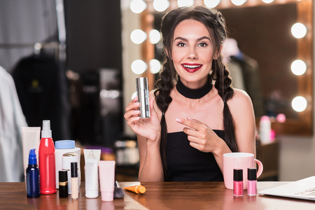 Modèle féminin joyeux à l'aide de produits cosmétiques Banque d'images - 81368736