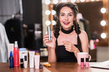 Vrolijk vrouwelijk model met behulp van cosmetisch product Stockfoto
