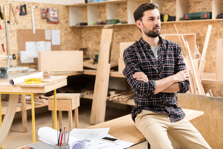 Pensive woodworker is resting at work