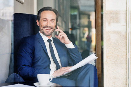 Glad male manager using cellphone for communication