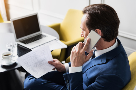 Serious businessman speaking by phone in workplace