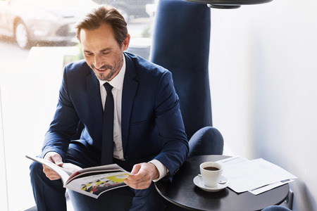 Joyful man in suit entertaining with journal in cafe Stockfoto