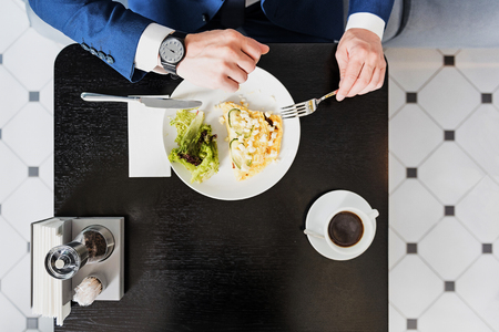 Busy businessman looking at watch during meal
