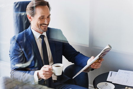 Cheerful businessman drinking coffee in cafe