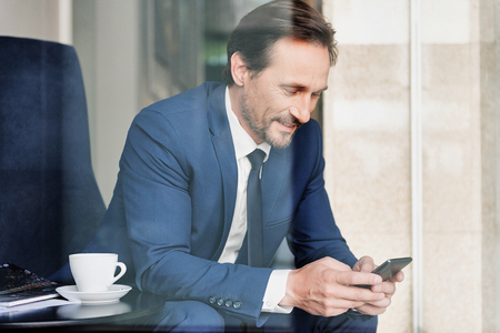 Portrait of concentrated middle-aged businessman typing message on smartphone. He is sitting in cafe near cup of coffee and smiling. View from glass window Фото со стока
