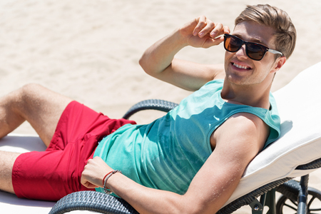 Cheery youthful man having rest on resort outdoor