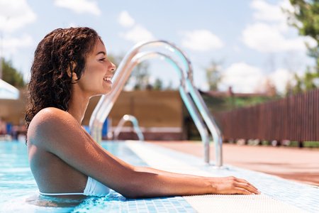 Cheerful youthful african girl swimming on summer resort