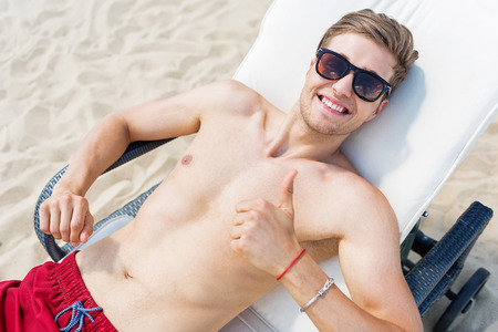 Jolly young guy having pleasure time while sunbathing outdoor Stock Photo