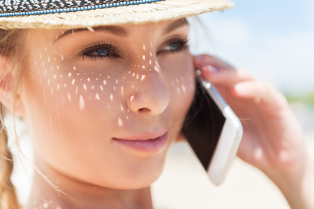 moderm: Close up of face of jolly young lady in summer hat holding mobile phone close to her ear. She is calling someone and looking to distance