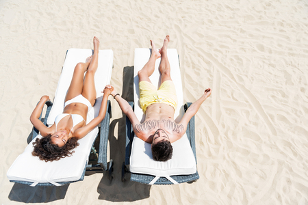 Youthful mulatto girl and bearded guy taking tan on beach