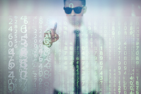 Abstract matrix. Concentrated man in sunglasses is working on transparent panel with numbers. He is pressing virtual button. Focus on screen