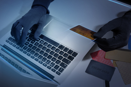 Computer and financial crime concept. Close up top view of hands of burglar wearing black gloves. Man is typing on laptop while holding bank card and stealing money