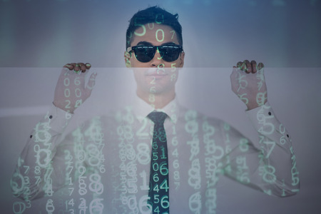 Computer codes. Pleasant man wearing sunglasses is looking at camera while leaning on transparent panel with numbers