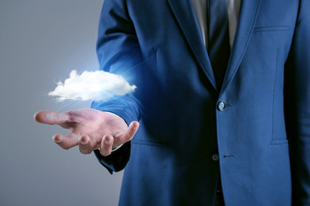 Technology concept for managed services and cloud storage. Man wearing suit is holding cloud in open palm facing upwards Imagens