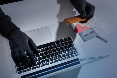 Payments system hacking concept. Close up top view of hands of unknown man wearing black gloves. Hacker is cracking pin code of credit card using laptop Stock Photo