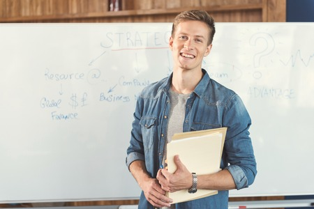 Joyful youthful guy working over new job strategies in office Stock Photo