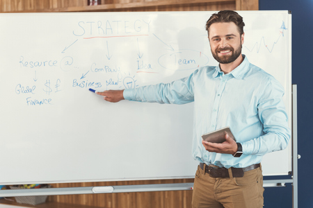 Cheery youthful bearded guy telling about job strategy at work