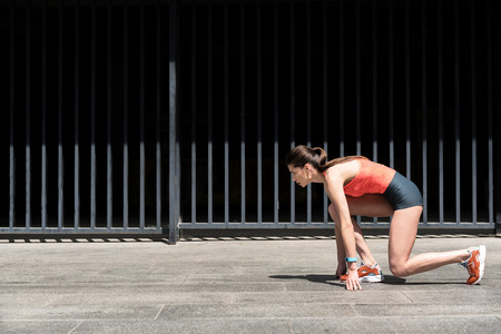 Serious female runner standing at starting position