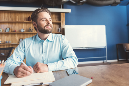 paper sheet: Cheery youthful bearded guy writing creative task in employer office Stock Photo