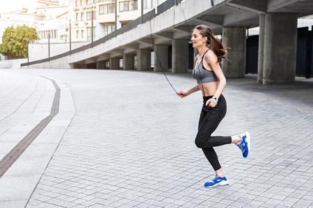 Gelukkige jonge vrouw training met springtouw Stockfoto