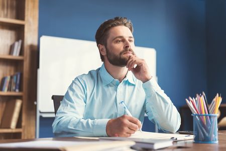 Thoughtful youthful bearded guy doing test for job employment Stock Photo