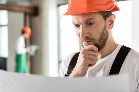 Thoughtful bearded builder looking at draft Фото со стока