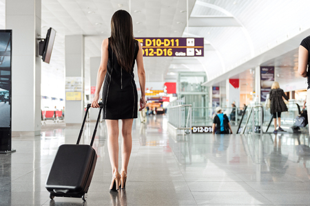Elegant attractive young businesswoman from behind is holding suitcase and going with it in international airport. Copy space in the right side