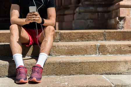 Sluit omhoog van lichaam van jonge sportmanzitting op steenstappen openlucht. Hij houdt mobiel vast en luistert naar muziek via oortelefoons. Kopieer de ruimte aan de rechterkant