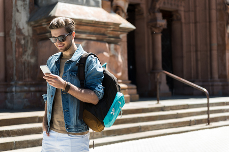 Happy youthful man with beard using gadget while sightseeing