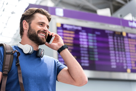 Cheerful attractive man is having communication on mobile phone