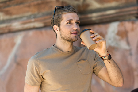 caffeine free: Thoughtful bearded youthful guy having coffee break outdoor Stock Photo