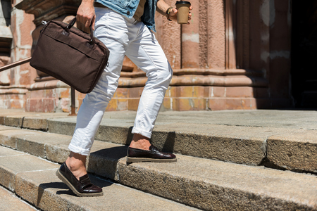 Close up of legs and hands of youthful guy scaling stone steps of old architecture building. He is carrying bad and cup of coffee Stock Photo