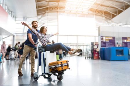 空港で楽しんで幸せな笑みを浮かべてカップル