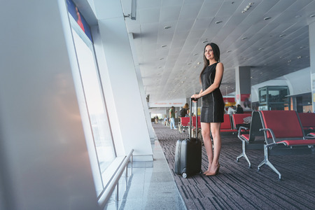 Attractive business woman is waiting for her flight with smile Banco de Imagens