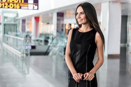 Joyful attractive brunette woman is waiting her flight Stok Fotoğraf