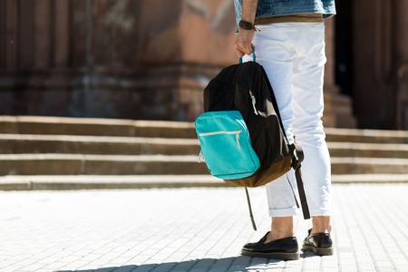 packsack: Close up of legs of young man standing on street square in front of building with stairs. He is carrying pack-sack. Copy space in left side Stock Photo
