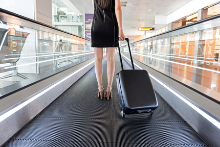 Close up of legs of graceful lady is standing with suitcase on modern moving walkway at international airport 版權商用圖片