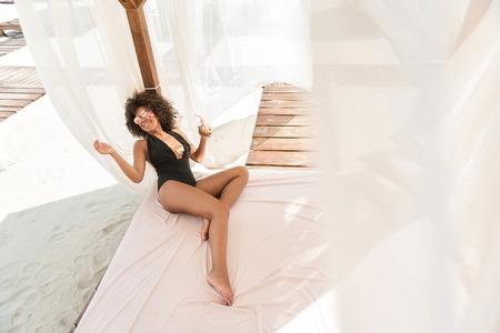 Jolly young mulatto girl enjoying her luxury rest on beach 스톡 콘텐츠
