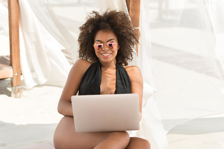 Jolly young mulatto woman using gadget on summer vacation