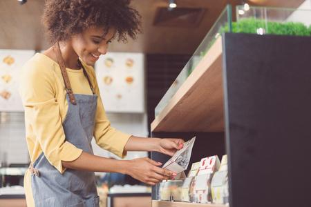 Felice giovane donna sta lavorando nel negozio di alimentari vegan Archivio Fotografico - 83155313