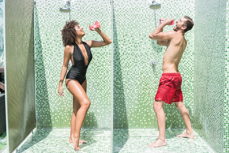 funny bearded man: Humorous youthful couple having fun while douching Stock Photo