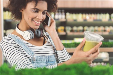 Enthousiaste jeune femme est de conversation sur smartphone Banque d'images - 83185930