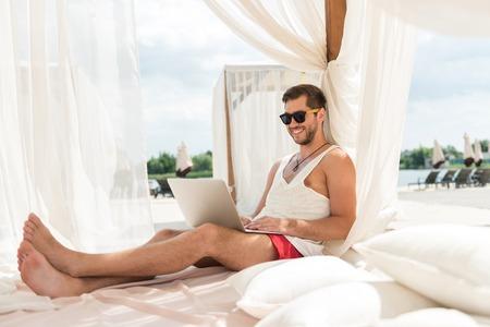 Happy youthful bearded man communicating via gadget on river beach Stock Photo
