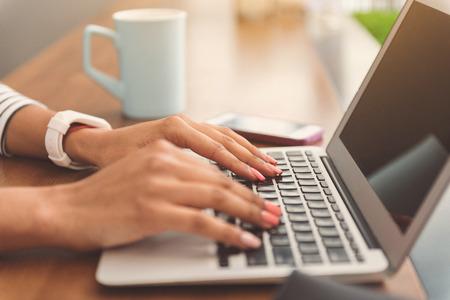 Pleasant girl is working on computer Banco de Imagens