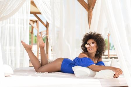 夏のビーチでリラックスした陽気なの若いアフリカ系女性