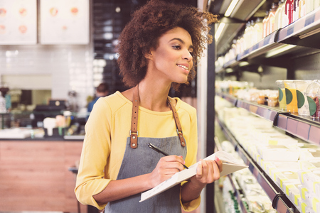 Positive concentrated girl is checking product at her shop
