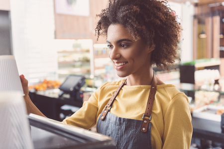Cheerful african waitress is working in organic store